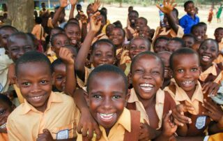 group of young african children smiling and waving towards the camera