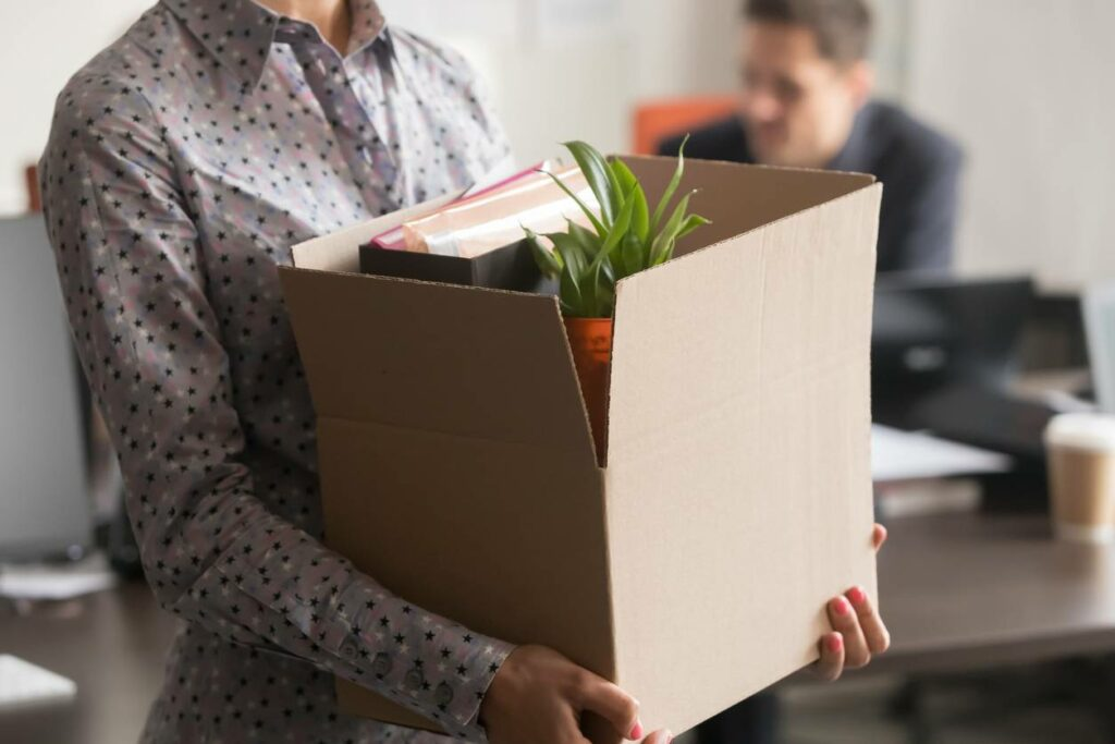 Close up view of a woman carrying a box of her personal belongings after quitting her nonprofit job